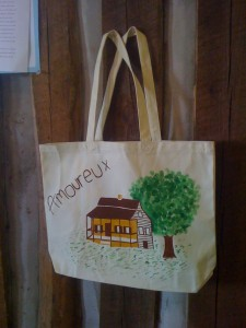 This is a photo of a canvas bag with a painted drawing of the Amoureux House.